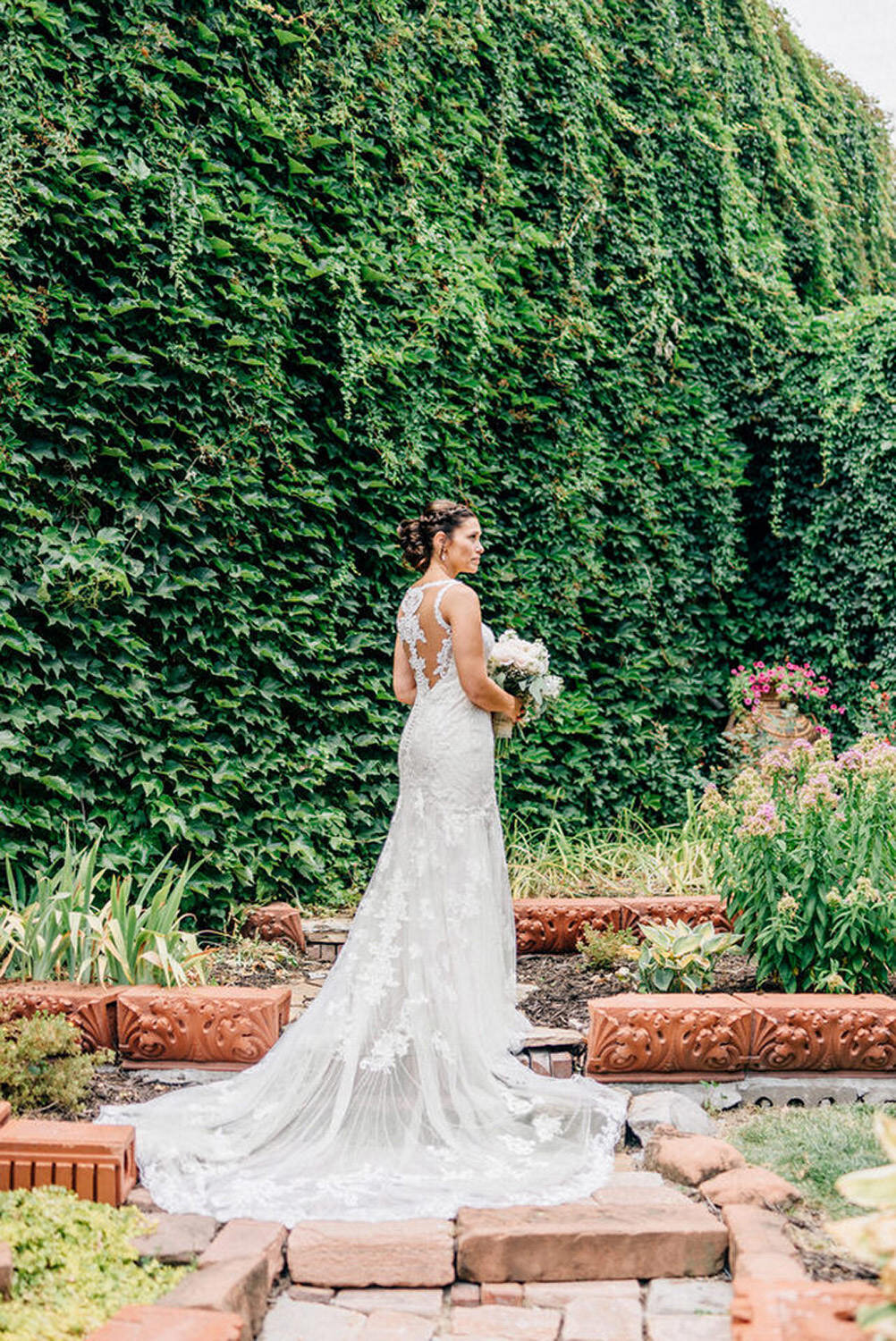 Beautiful bride poses in front of ivy wall in omaha