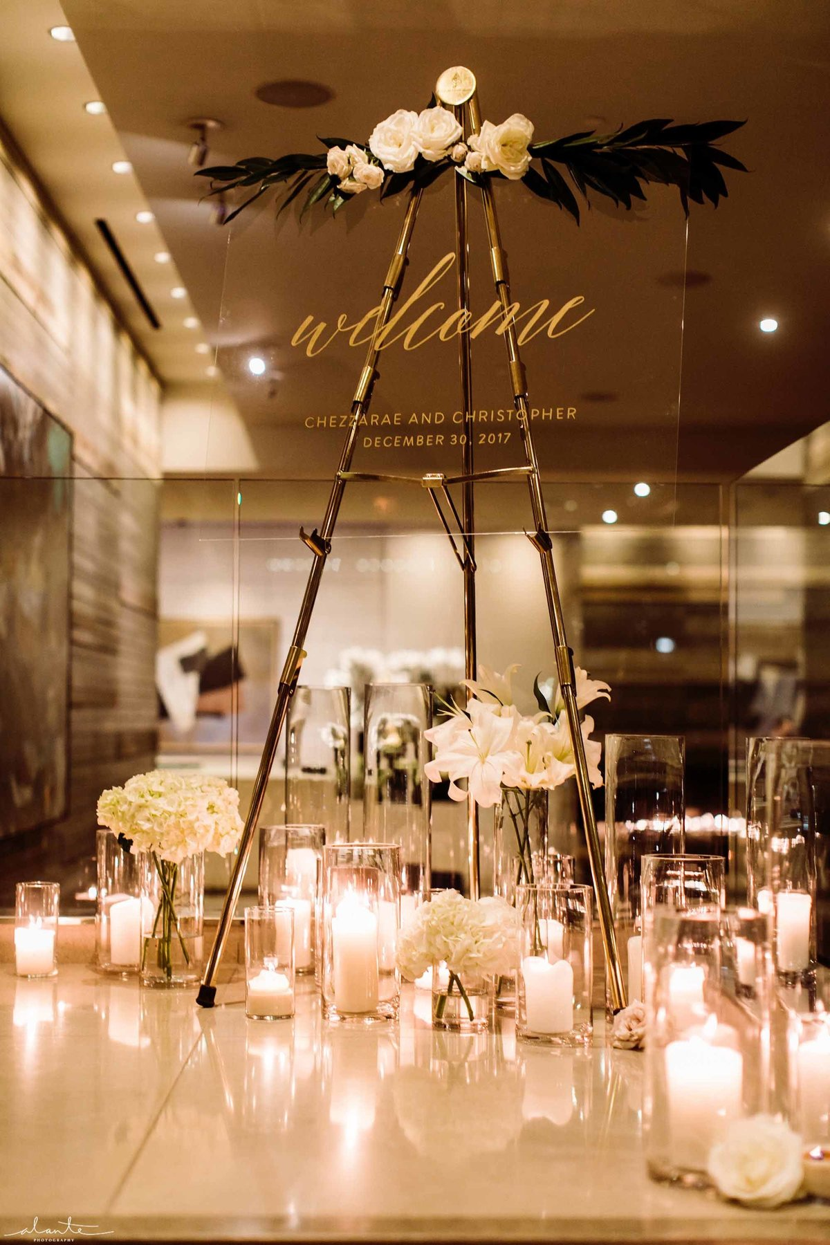 Lucite sign to welcome guests surrounded by hurricane candles.
