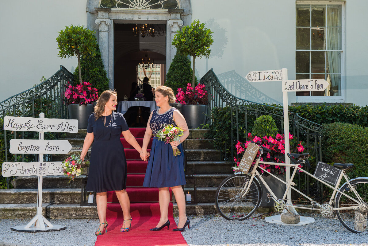 Gay brides in navy dresses on red carpet, holding hands beside tandem bicycle