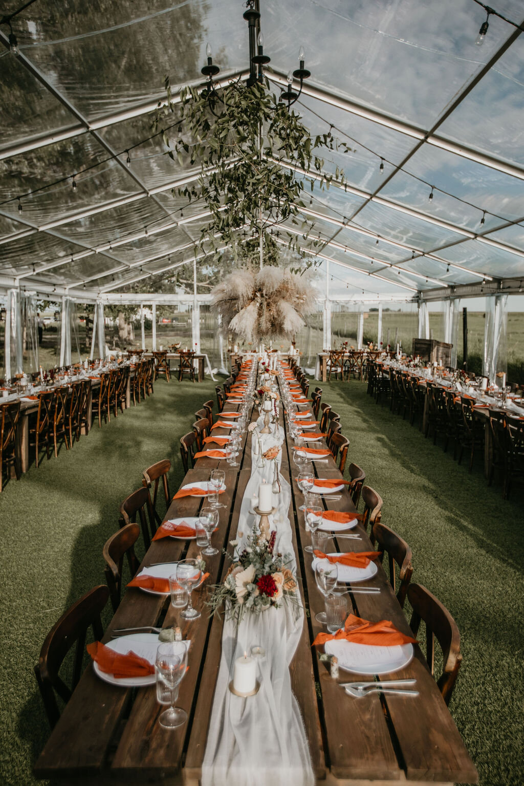 inside a clear tent with wood tables and chairs, cheesecloth runner and florals