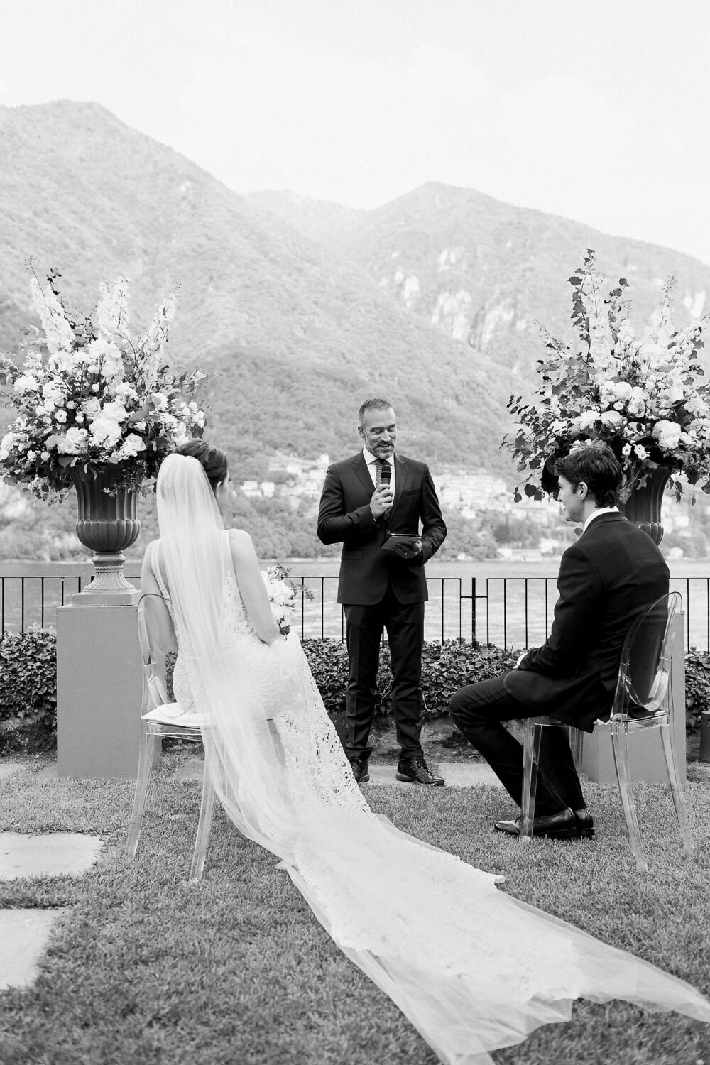 bride and groom sitting at ceremony altar in front of Lake Como wedding destination