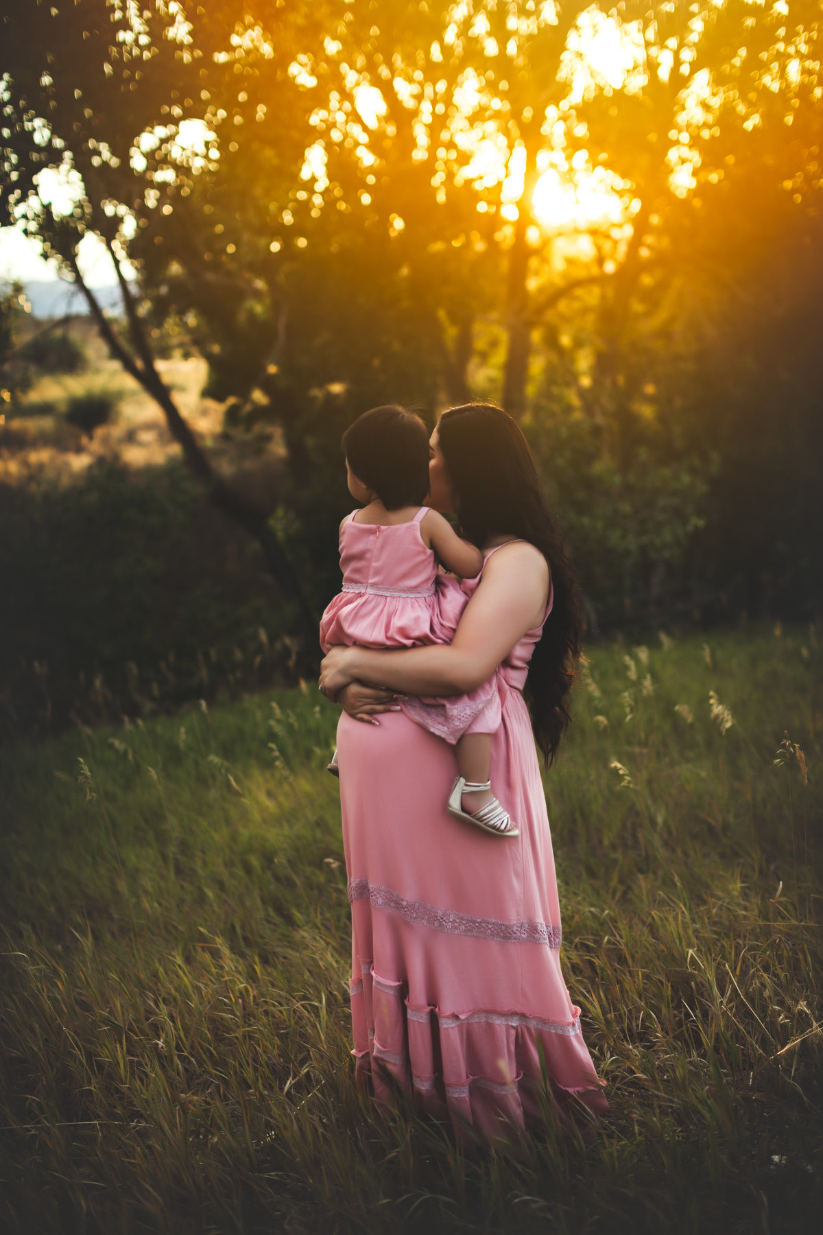Mother and daughter maternity pictures outside at sunset