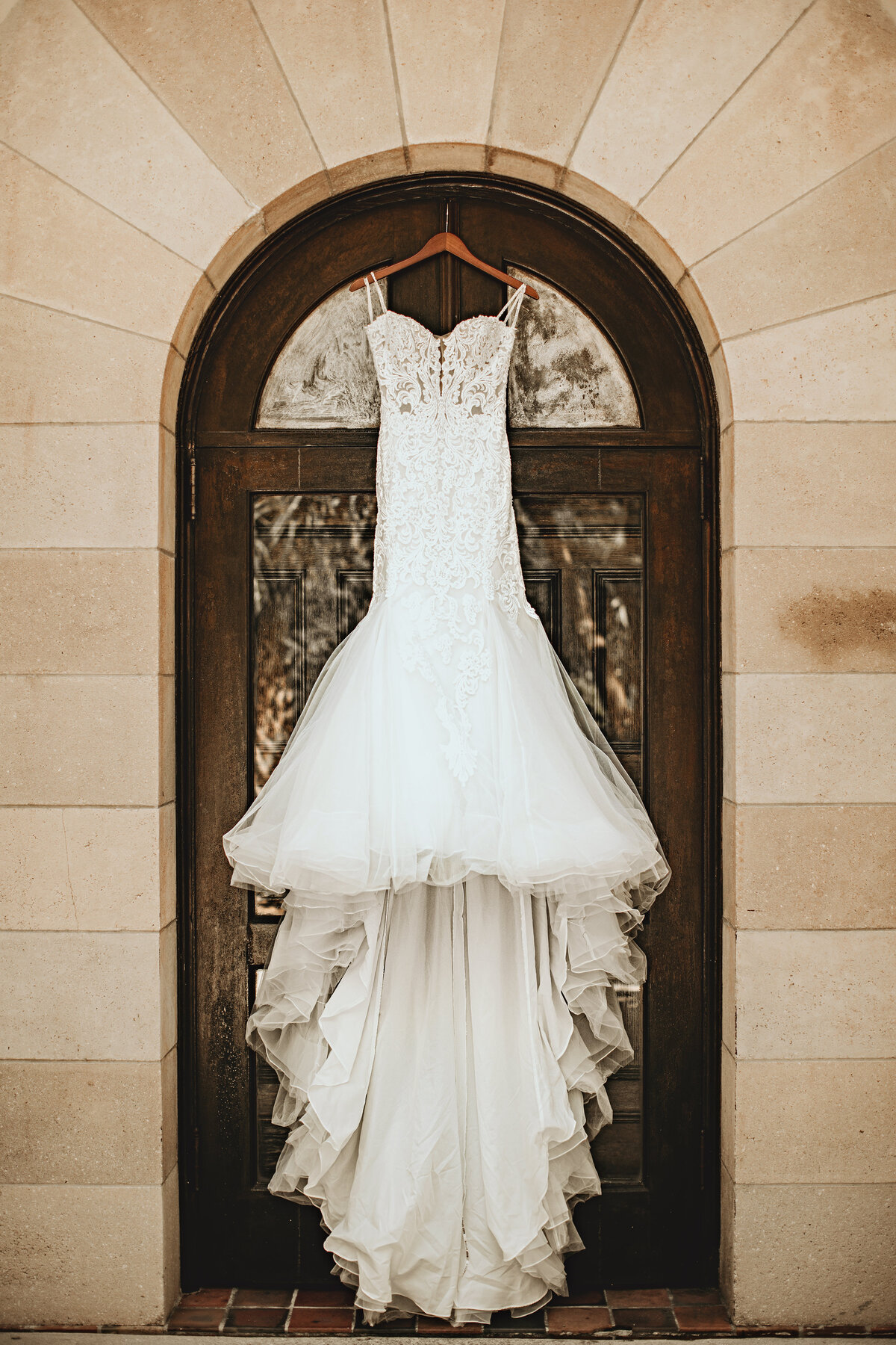 An image of the bride's lovely wedding dress and long train hanging from the top of a vintage arched door and stone arch by Garry & Stacy Photography Co - St Petersburg wedding photography