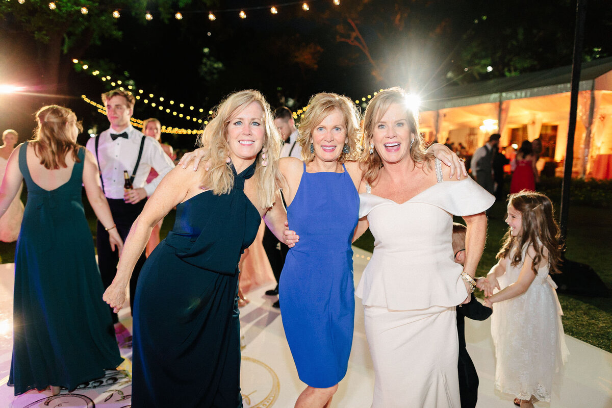 three women posing for photo smiling at outdoor night wedding reception
