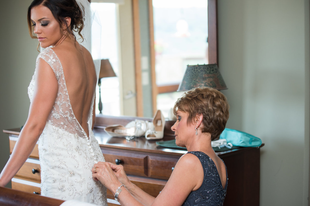 mother helping put on bride's wedding dress
