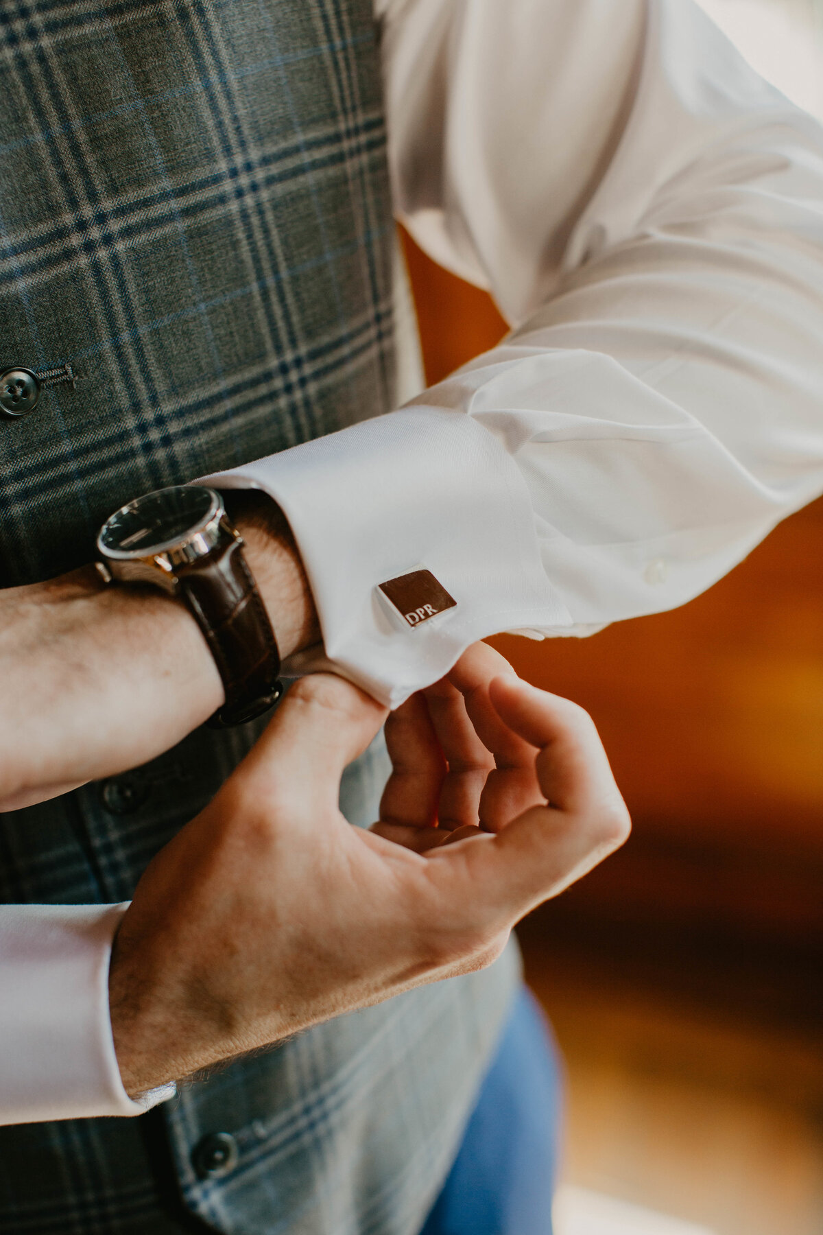 A picture of a closeup view of the groom adjusting the cuff link on his dress shirt as he dresses for his wedding ceremony by Garry & Stacy Photography Co - St Petersburg Florida wedding photography and videography