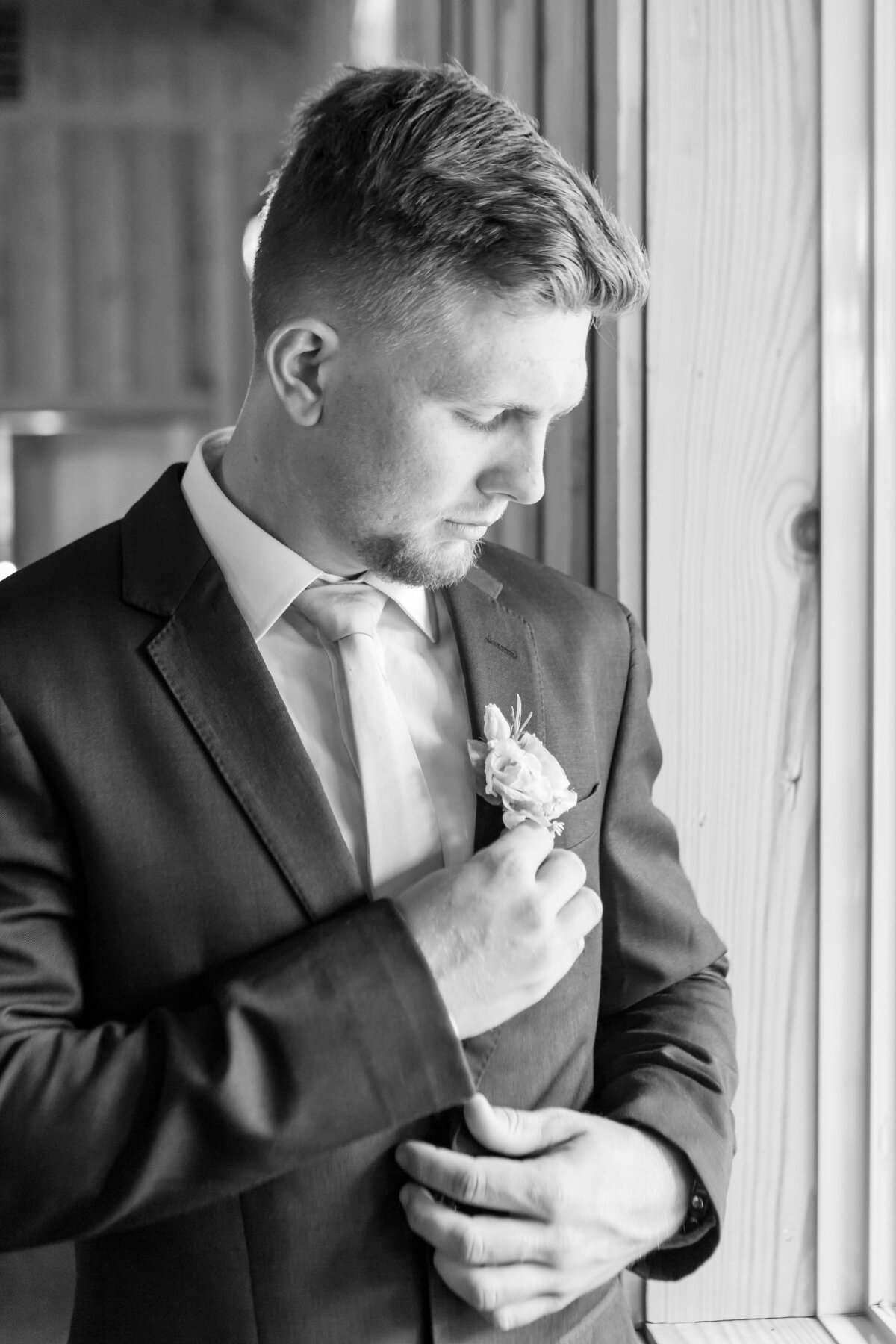 Groom Adjusting His Boutonnière Next to a Window
