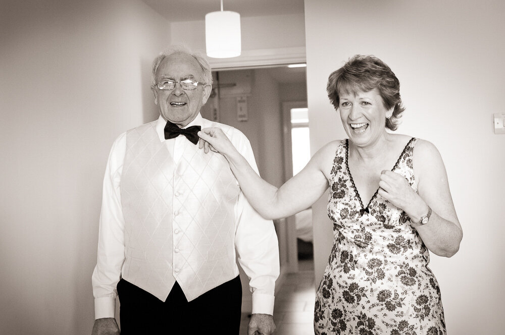 father of the bride in black tie and white waistcoat laughing with his wife