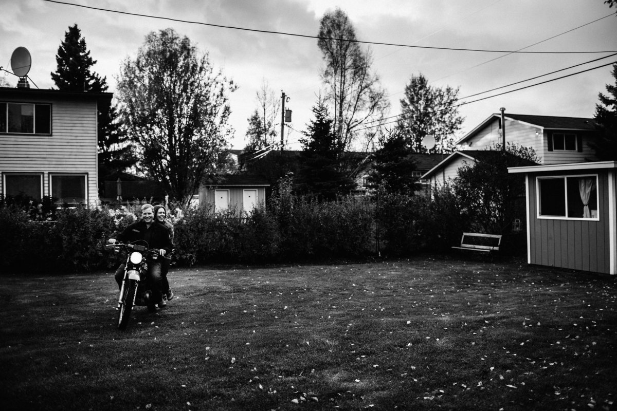 man and woman riding on motorcycle in backyard