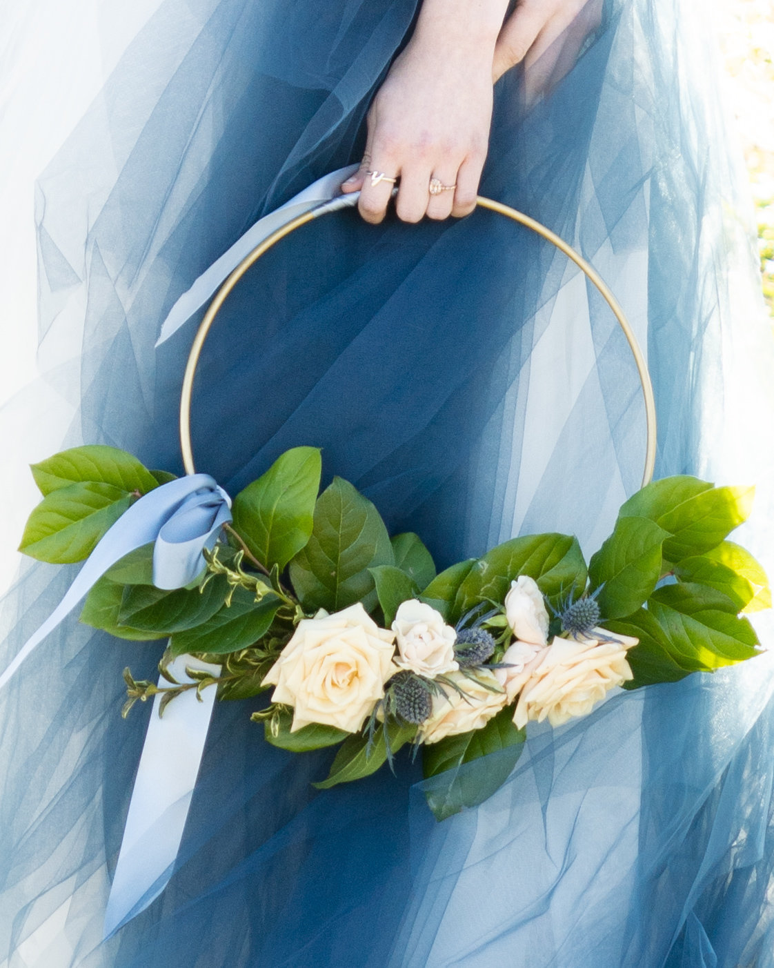 Detail shot of loop bouquet with roses in front of a white dress with blue tulle
