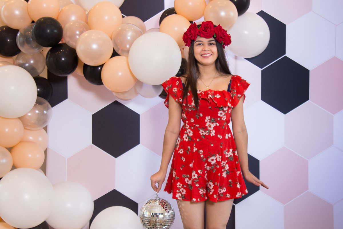 balloon backdrop and lovely girl posing with a disco ball fronbt of a cool backdrop