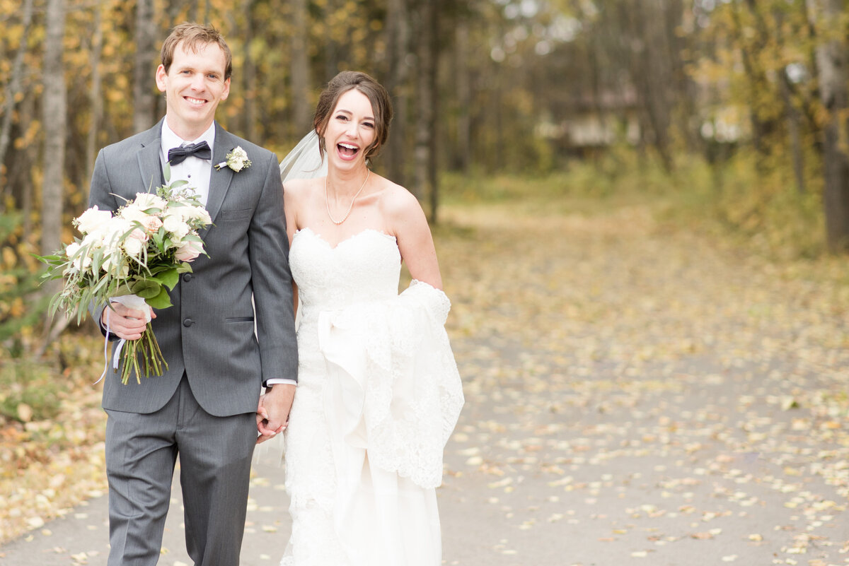 A bride and groom walk through leaves during their fall wedding in Thunder Bay
