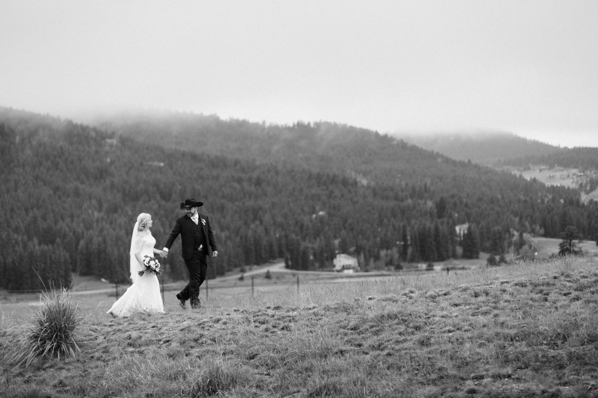 A newly wed couple walking up a hill together.