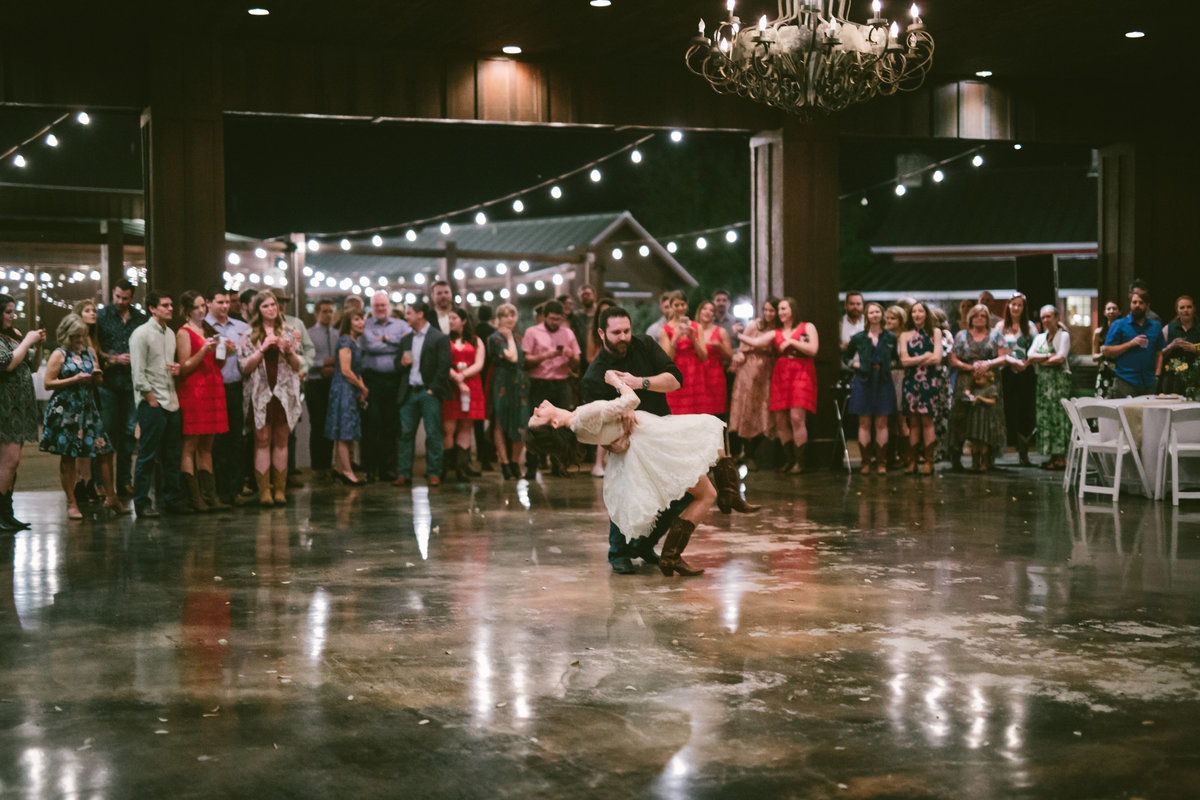 Groom dips bride during first dance at reception while guests cheer on at The Grande Hall at Hoffman Ranch wedding venue