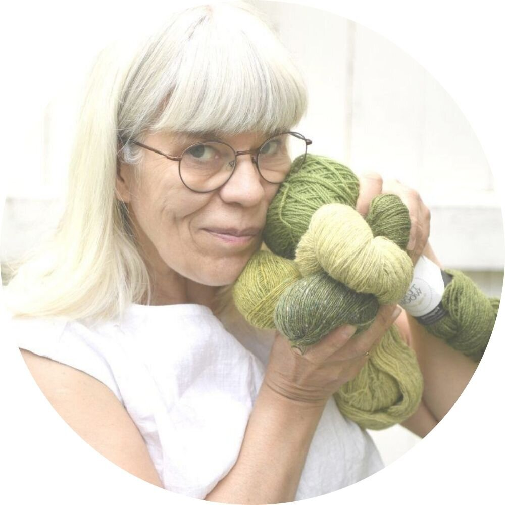 Tuija is smiling and holding green skeins of yarn next to her cheek.