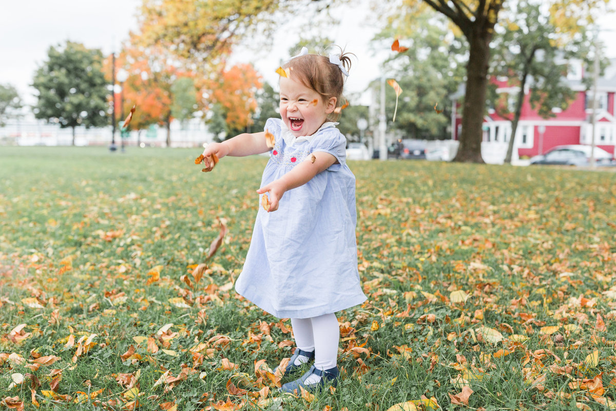 Toddler Girl throwing leaves in the air