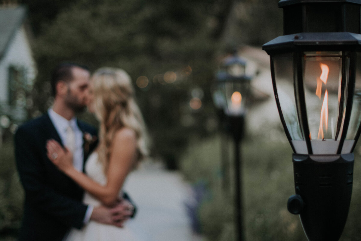 Streetlight-with-bride-and-groom-blurred-in-background-kissing