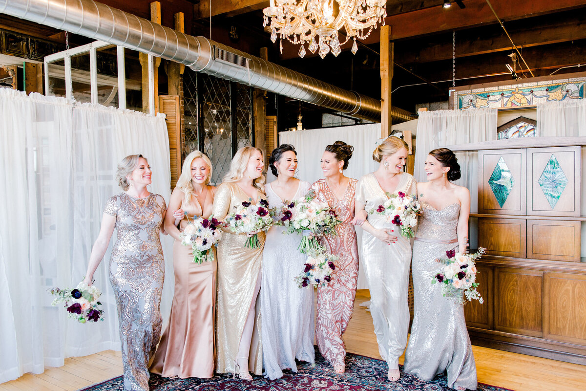 bride with bridesmaids laughing in the getting ready room in Salvage One venue in Chicago