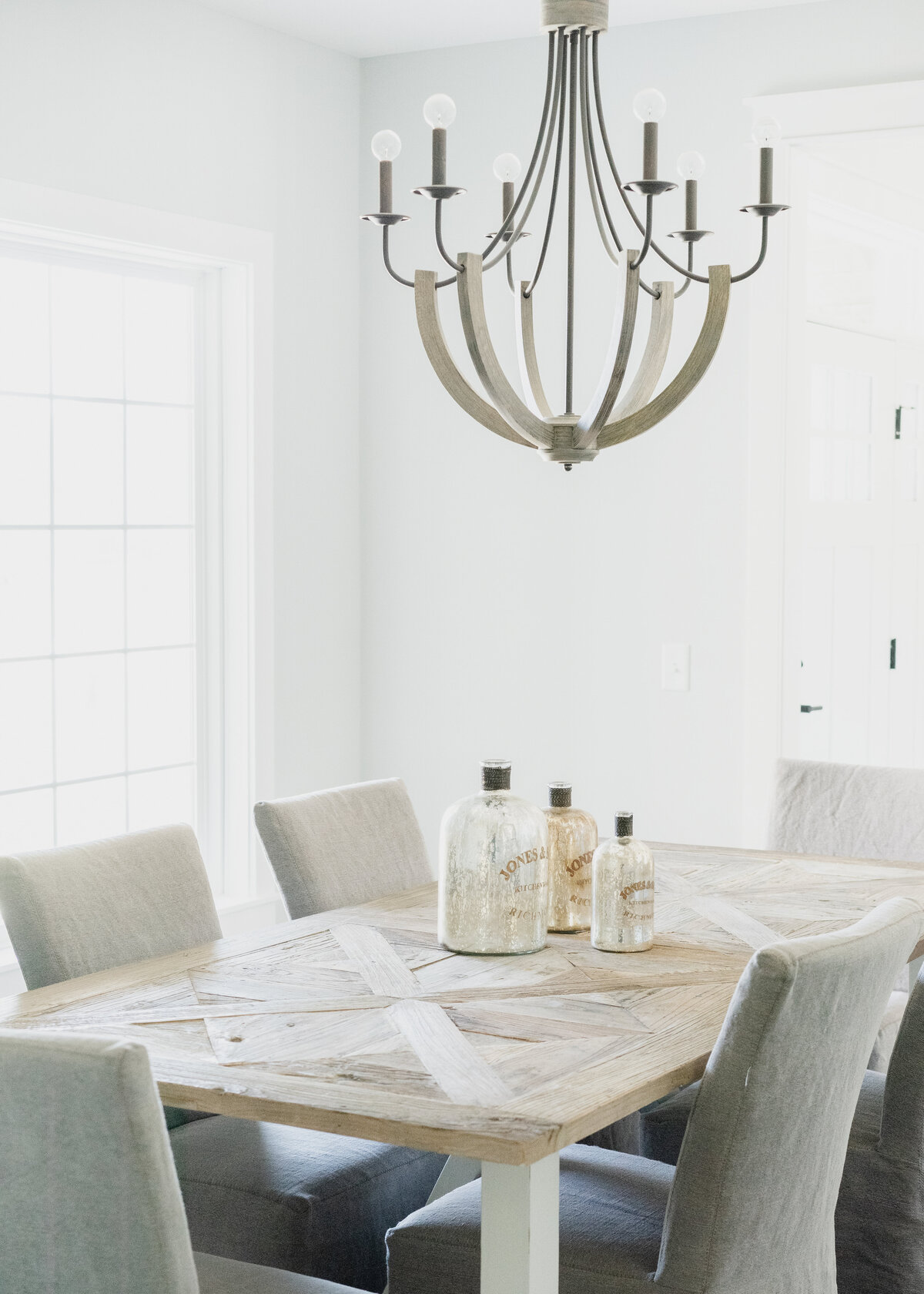 A parquet dining table is in a white room with grey dining chairs under a boho chandelier with apothecary interior decor.