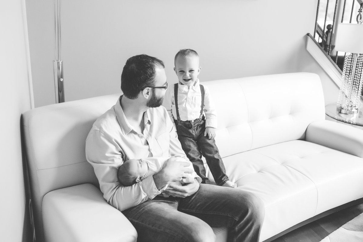 Father holding newborn baby son and looking at toddler son on couch {Mississauga Lifestyle Photographer}