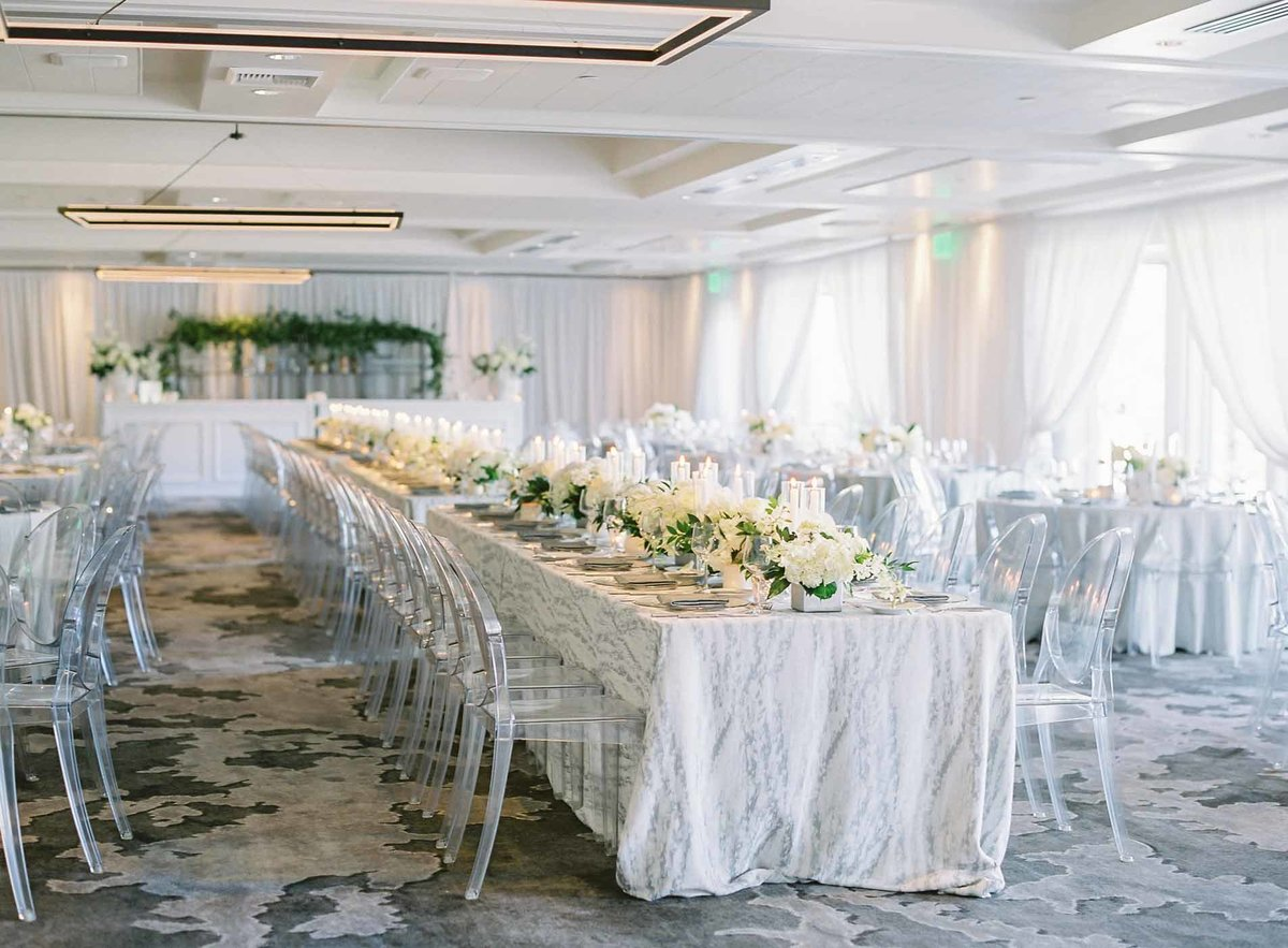 Lucite Ghost chairs line the long tables at this elegant white Overlake golf and country club wedding
