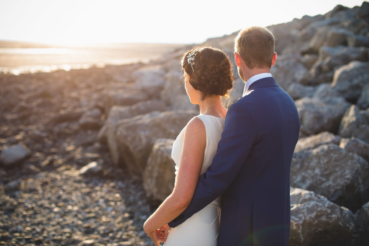 bride and groom at the beach at golden hour