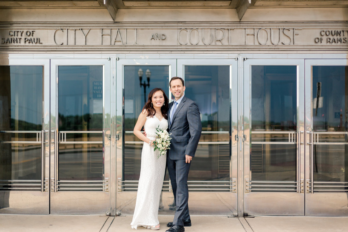 bride and groom stand in front of doors of city hall st paul minnesota
