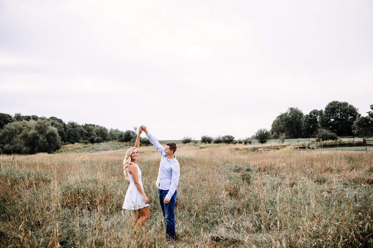 Engaged couple dancing in field in Buffalo, New York