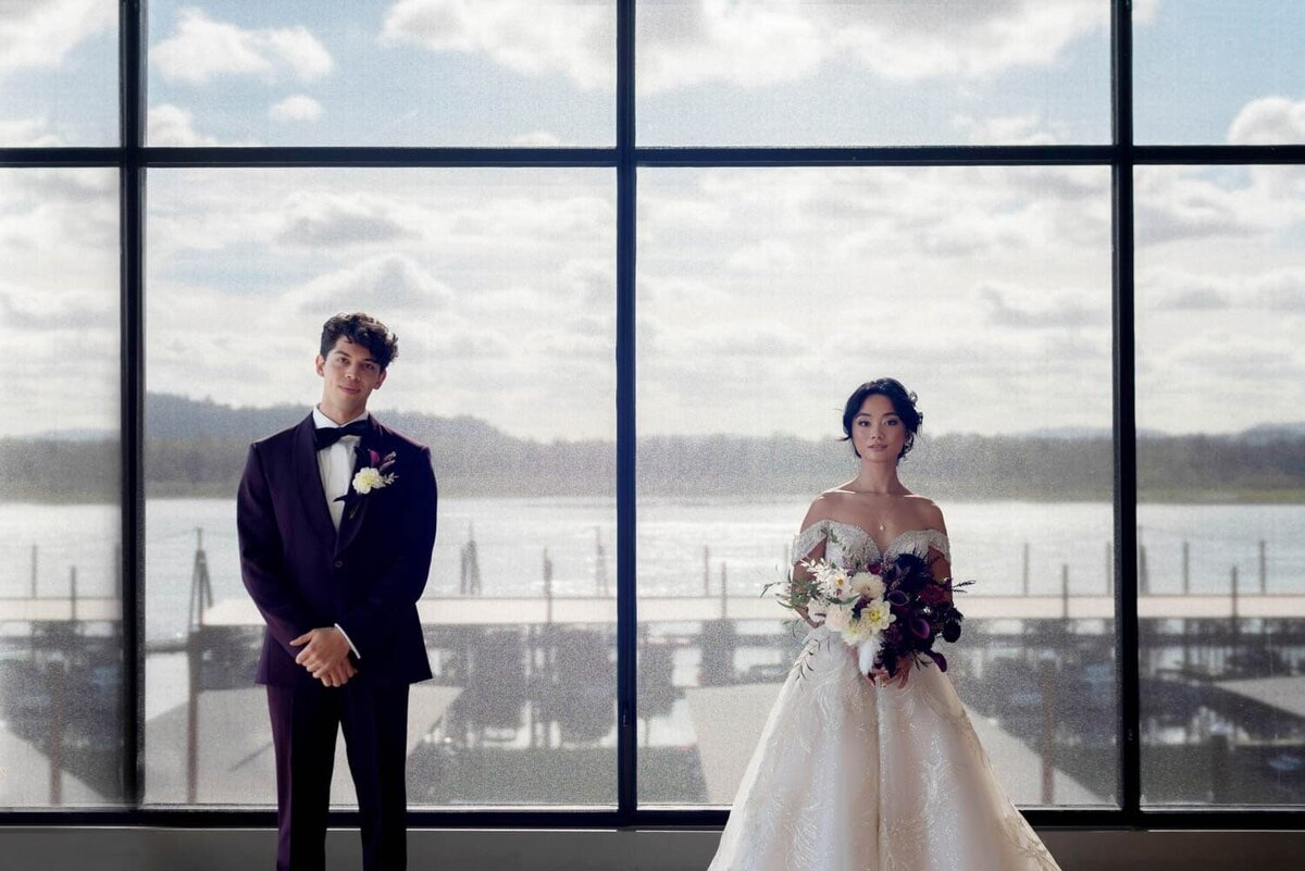 a stylish bride and groom stand in front of windows overlooking a marina of the columbia river