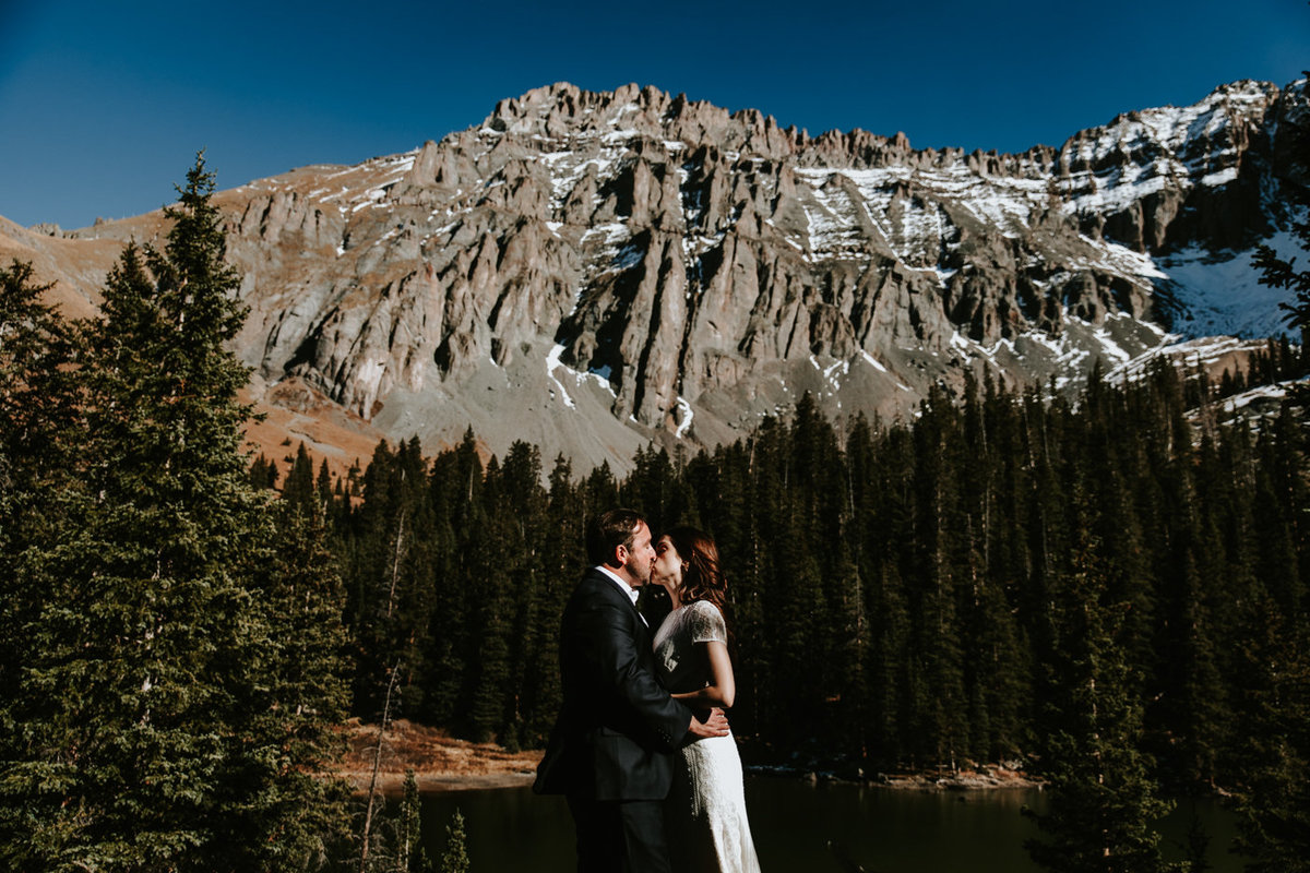wedding couple kissing in front of a mountain at The Observatory at Alta Lakes in Telluride, Colorado