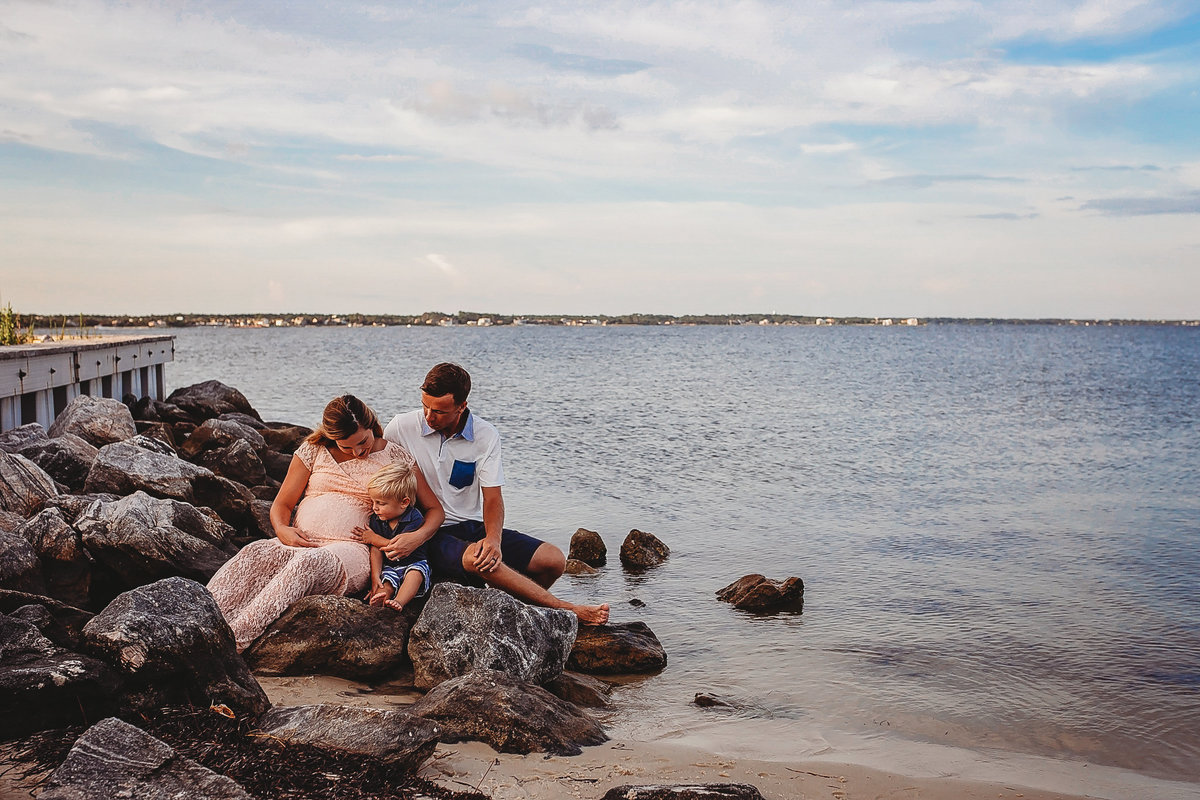Family sits on rocks for maternity session