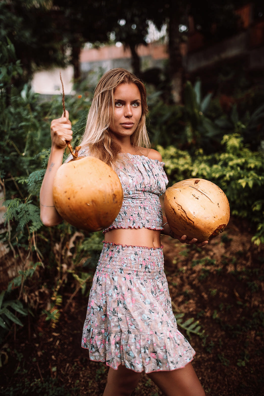 blonde girl in bali picking coconuts