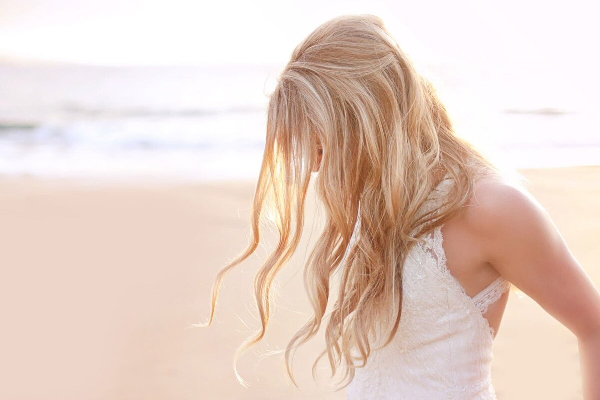 Bride with wavy hair looks down in the sand as hair obscures her face