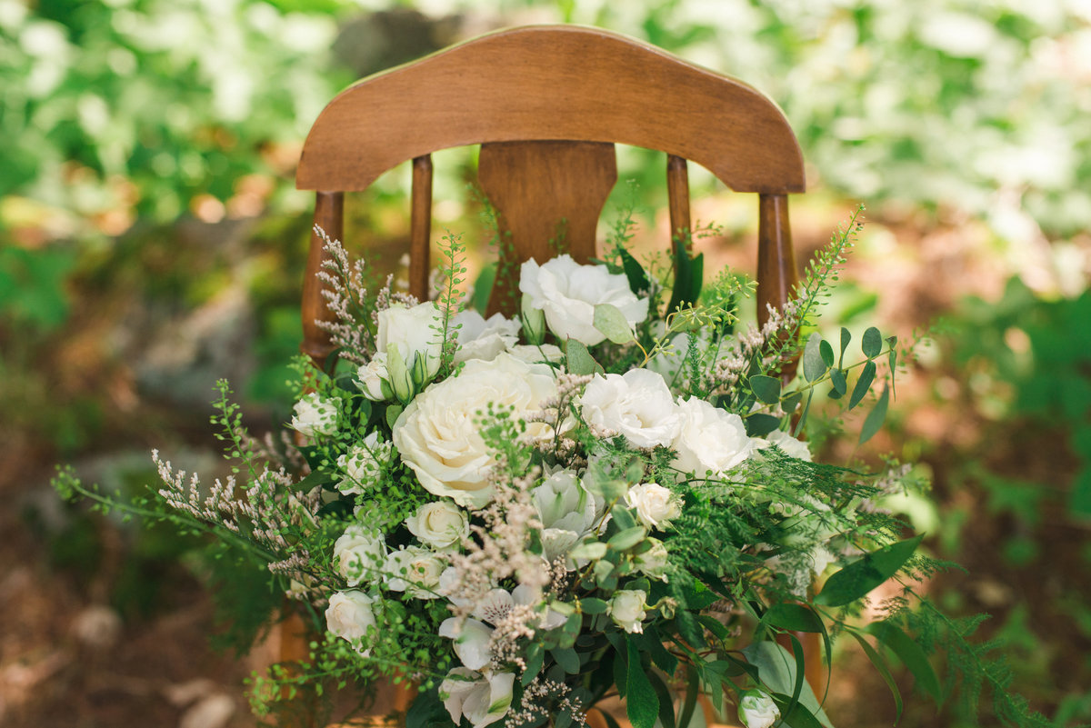 Green and white wedding bouquet sitting on vintage wood chair in the forrest