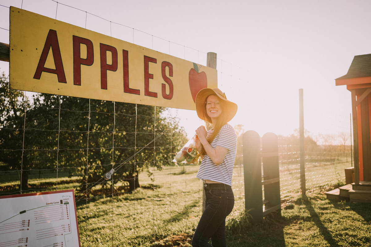 Alexandria Salmieri standing in front of large apples sign at sunset holding bag of apples she picked at Center Grove Orchard in Iowa