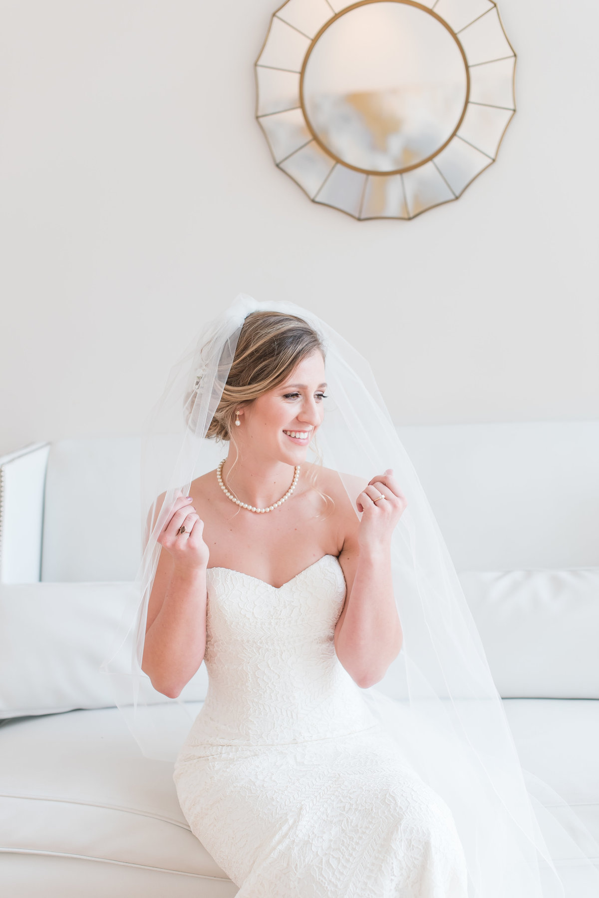 A bride wearing a strapless dress with cathedral length veil in front of a white wall and sitting down on a white couch smiling at the Glass Box at 230 in Raleigh