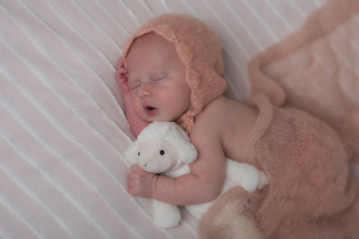 baby girl cuddling little sheep doll