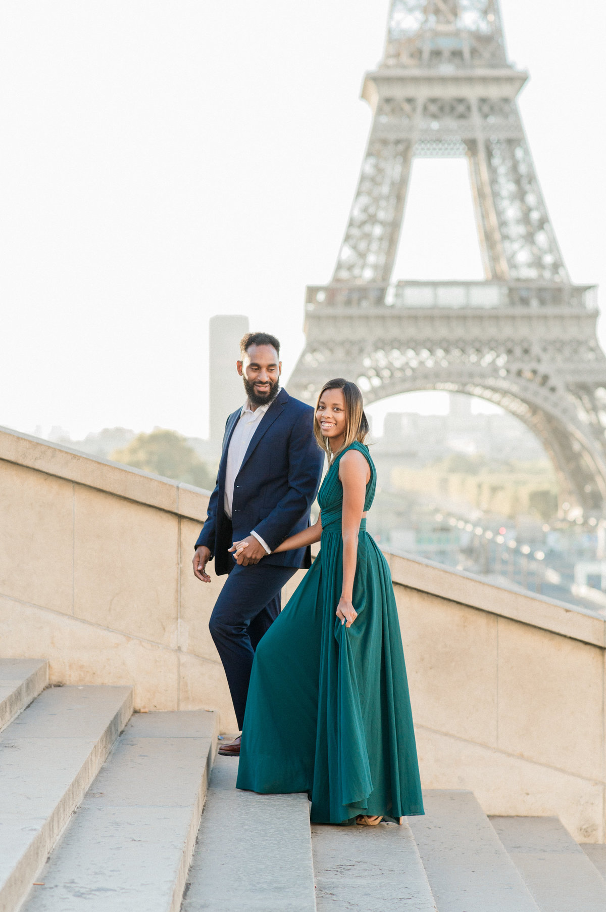 engaged couple walking up stairs at trocadero with eiffel tower in background