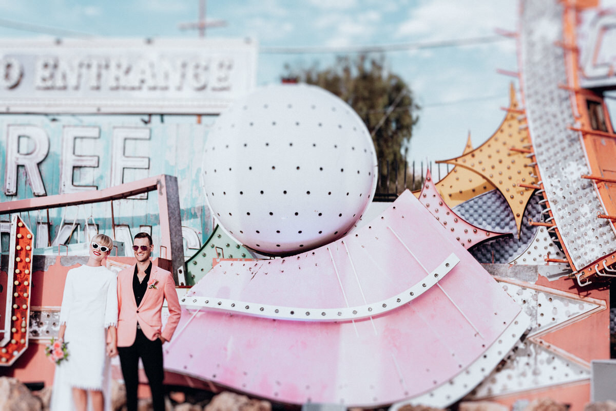 las vegas elopement photographers couple poses in front of vintage marquee