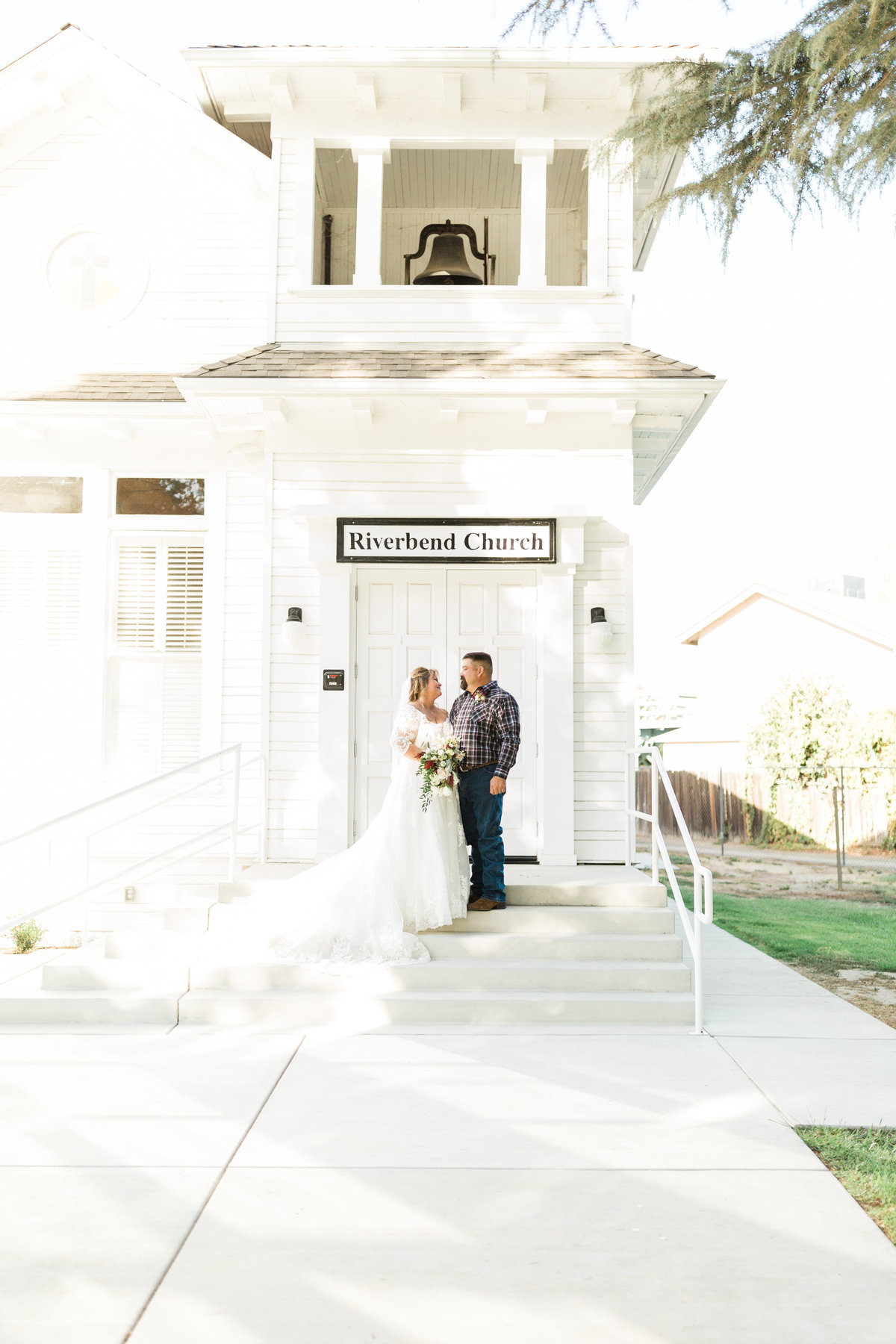 newlywed couple posing in front of a small white church in Kingsburg