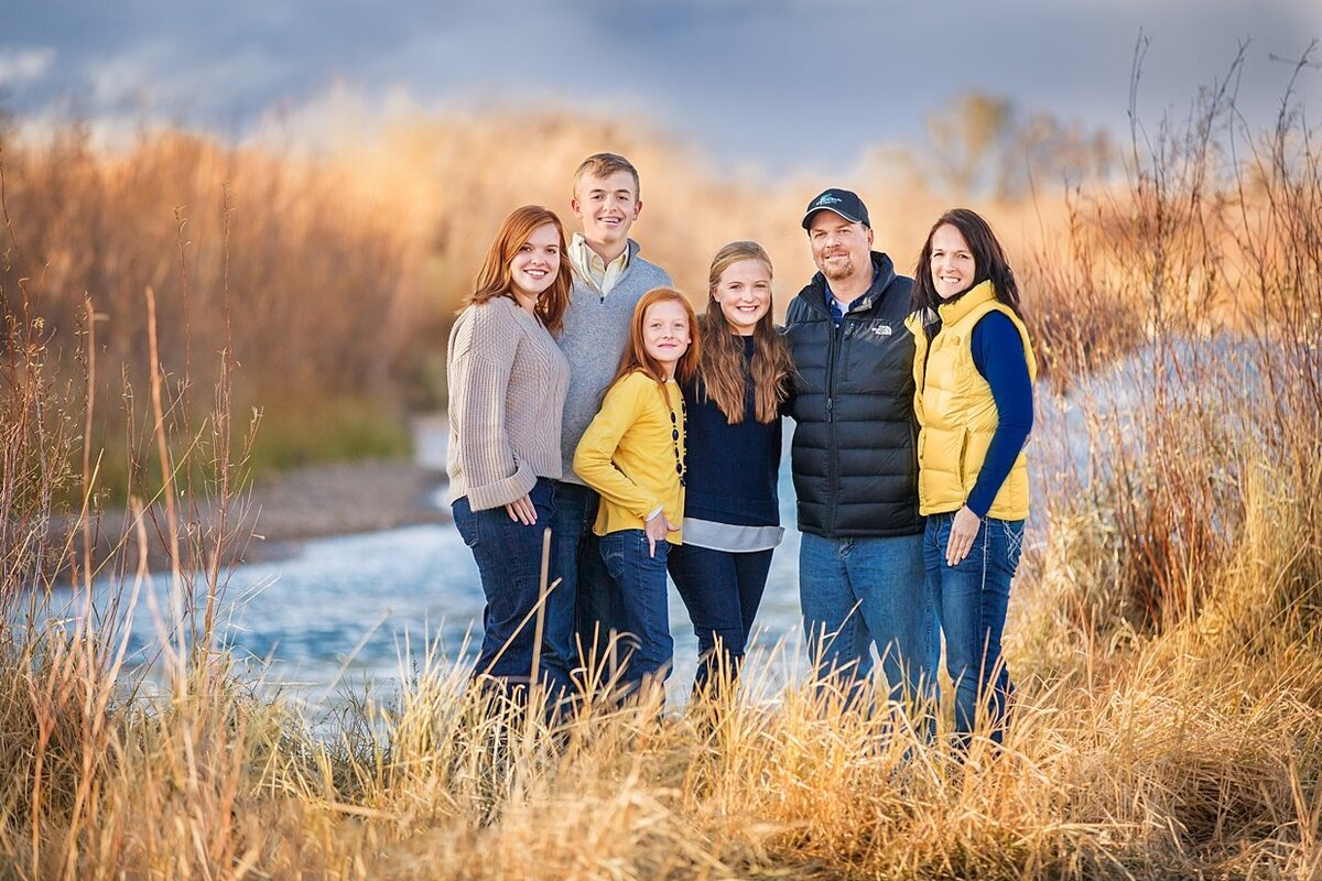 With hues of blue and yellow on a winter day next the Laramie river stands a family dressed warmly together on a cold winters day.