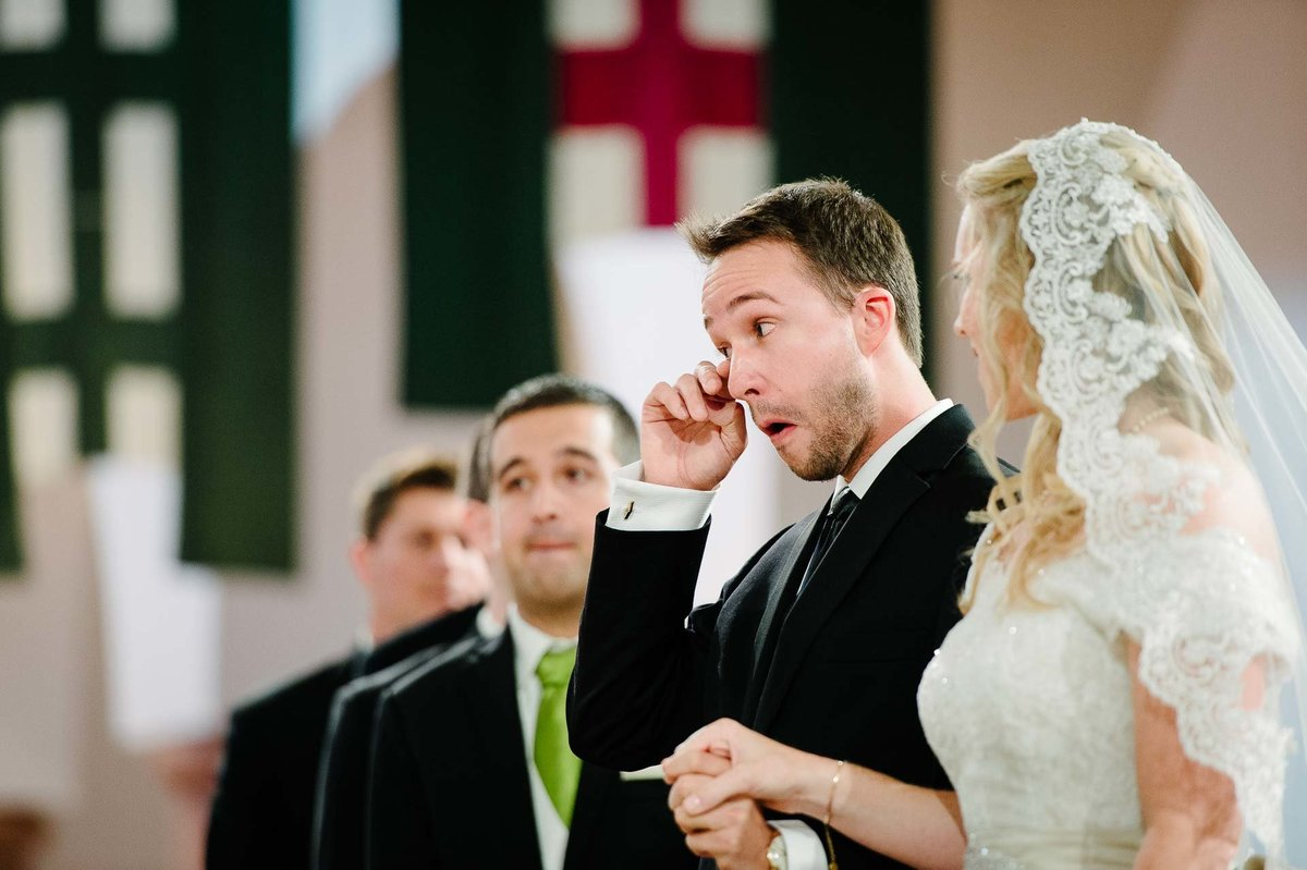 groom being emotional during wedding ceremony at saint ann church in dallas