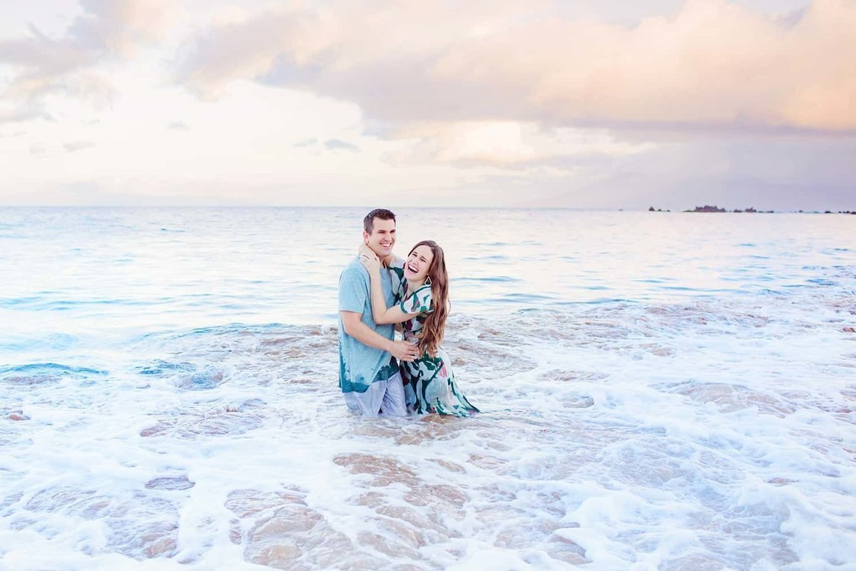 Maui engagement portraits featuring couple laughing in the ocean