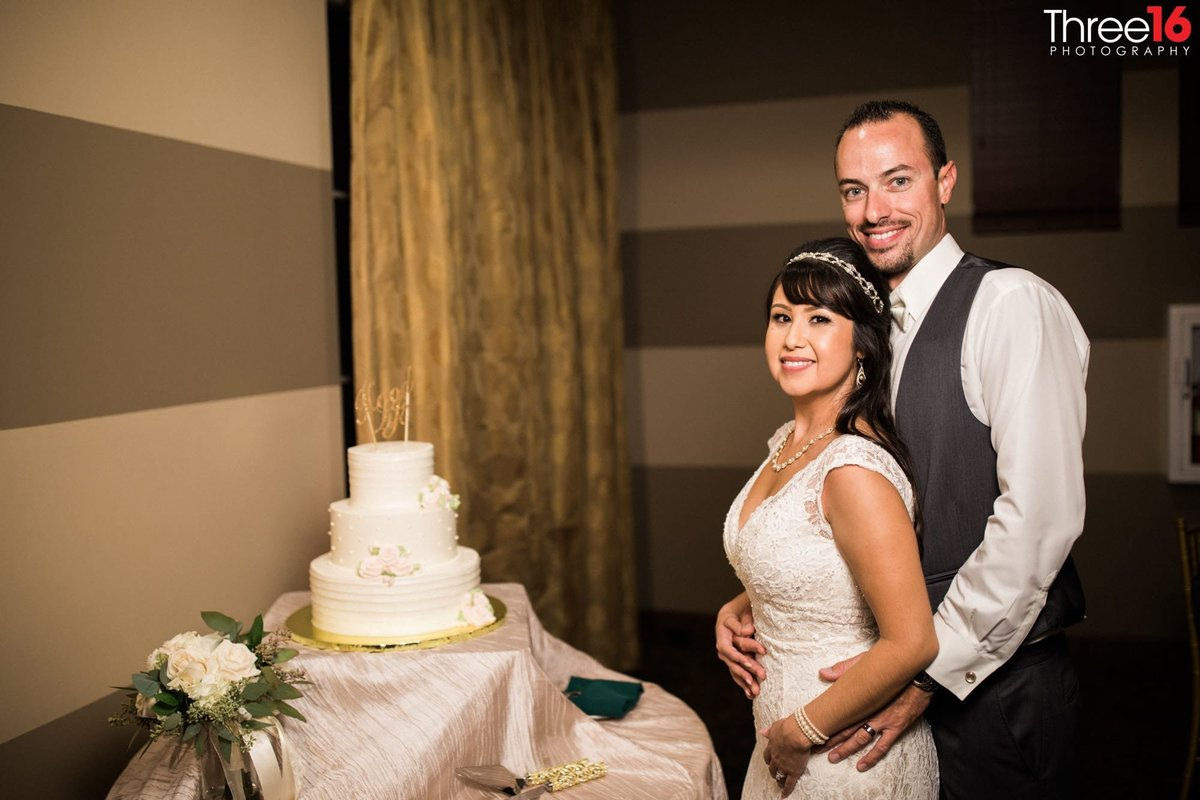 Bride and Groom pose with the wedding cake