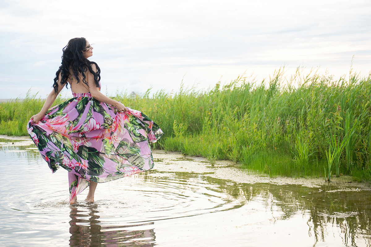 woman walking through a pond twirling her dress