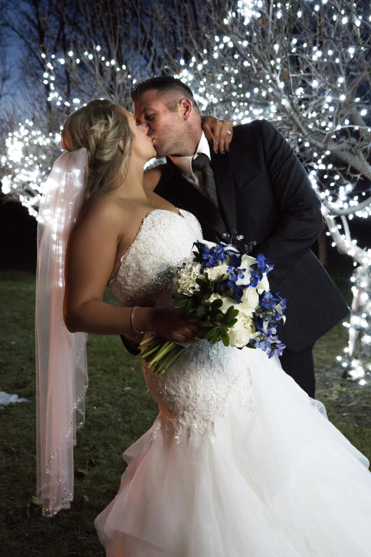lit trees at meadows barn, sioux falls, bride and groom dip and kiss