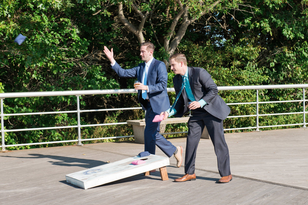photo of groomsmen playing bag toss during wedding reception at Pavilion at Sunken Meadow