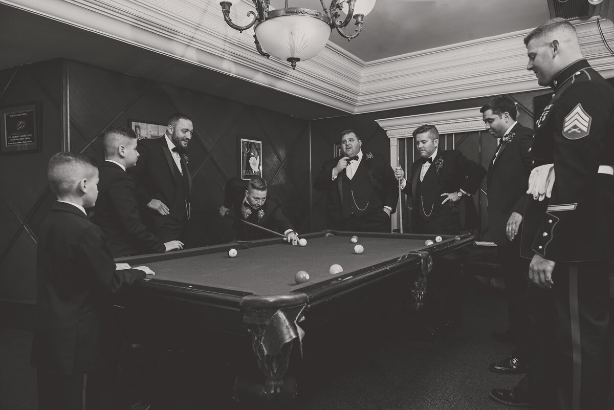 black and white wedding photo of groomsmen playing pool in billiards room at The Carltun