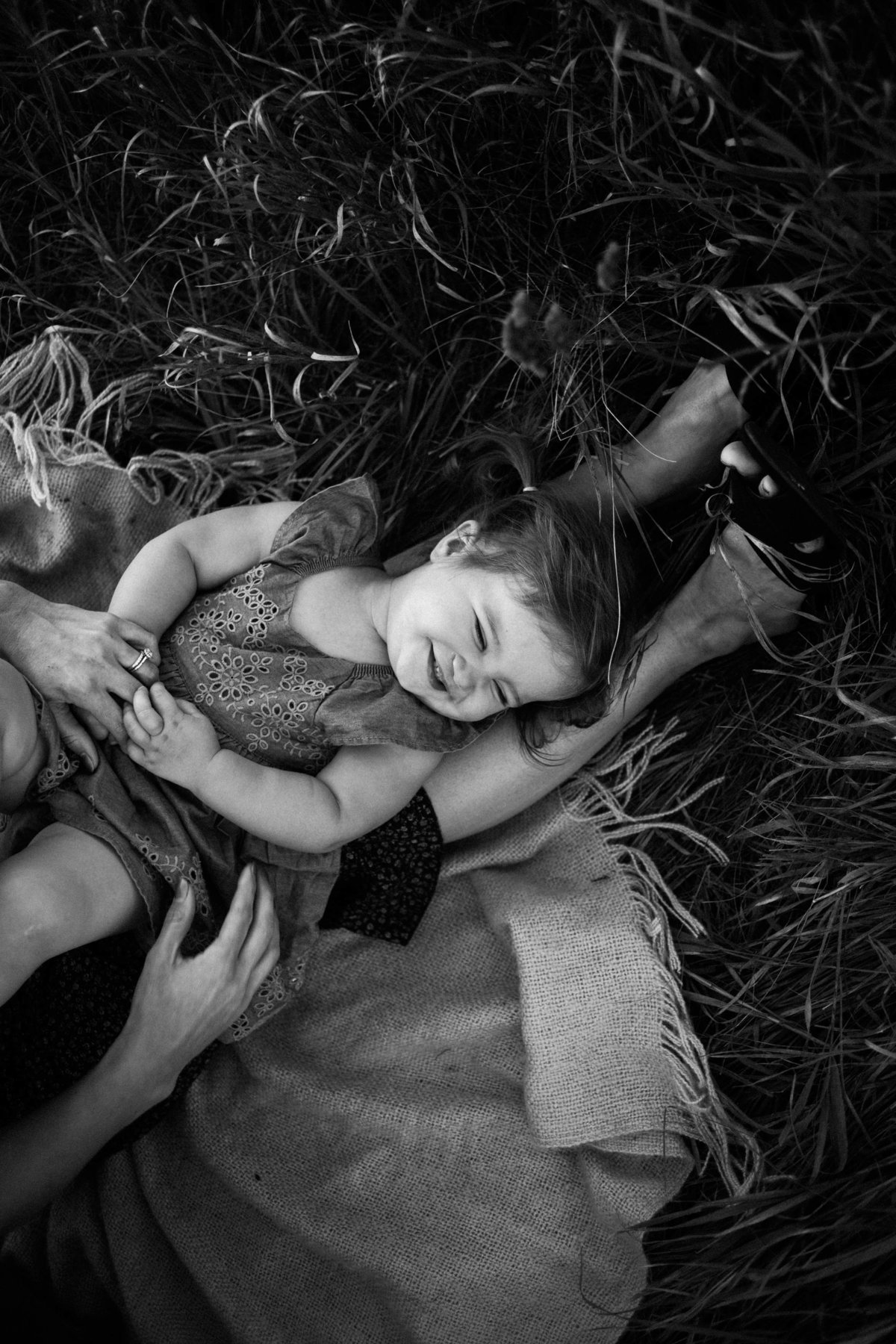 Mom tickling her baby girl on a blanket in an open field