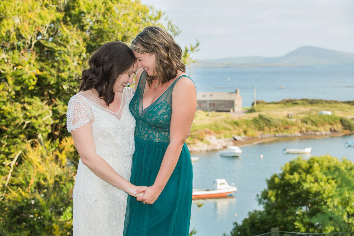 bride in vintage, beaded wedding dress embracing her bridesmaid wearing a jade green dress overlooking Castlecove Pier in Kerry
